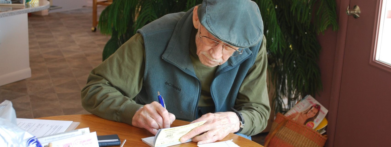 This is an image of Clayton Brockel, KPC's founding director, writing a check to provide for a donation to student scholarship endowments his family supported.