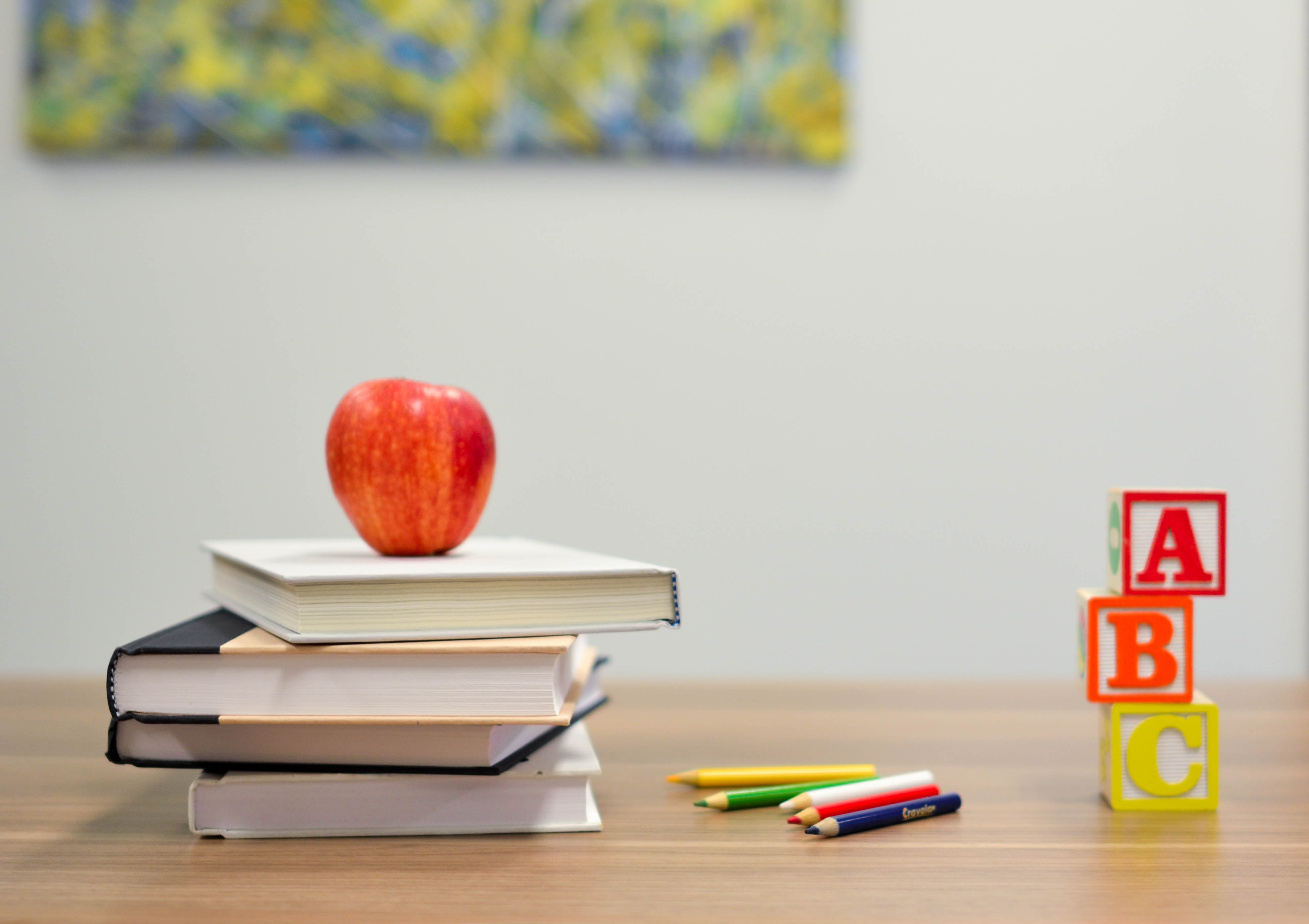 Stack of books with an apple on top, colored pencils and A,B,C blocks. sitting on a table.