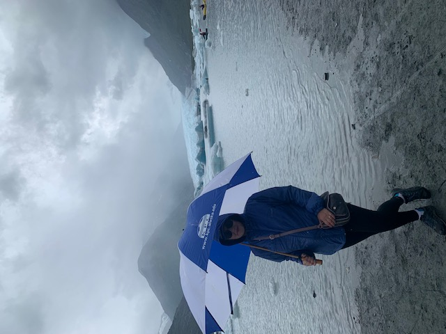 Person standing in front of a glacier holding an umbrella