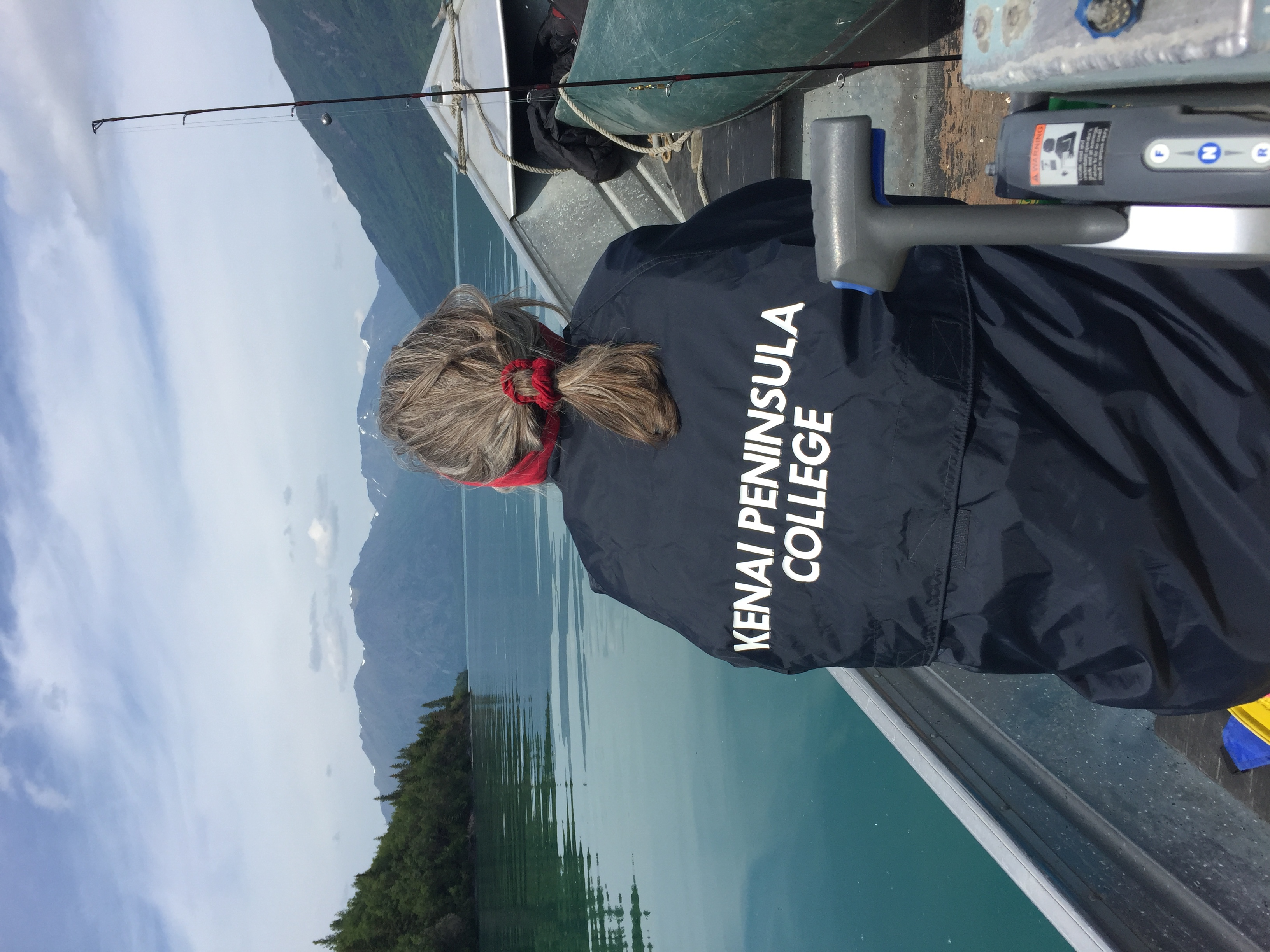 Person wearing a Kenai Peninsula College coat riding a boat on a lake with Moutians in the background