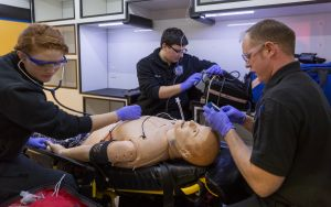 two male and one female paramedic students with manakin