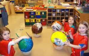 three female kids with globes in classroom