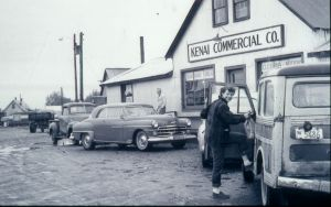 three 1950s cars with woman in front of Kenai Commercial Co.