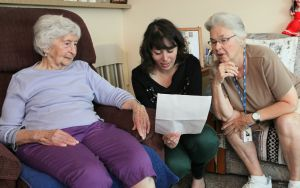 two older women and one younger woman explaining written instructions