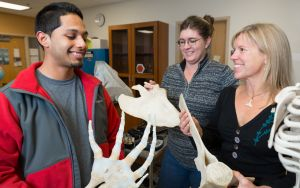 Female teacher with whale bones with male and female students