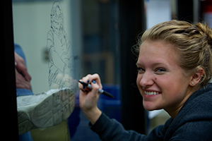 Smiling female student writing on glass window