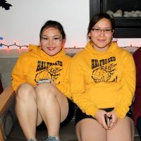 Two Alaska Native college girls sit on a couch together, smiling at the camera.
